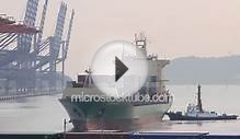 Large container ship pushed by tugboat